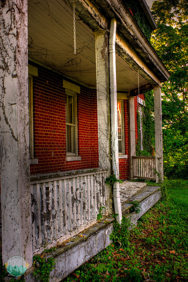 Never Sold<br /> A closeup view of one of the homes in Fort Thomas that has never sold that was part of the old Fort.  Stuff growing up and over and a railing that has seen better days and taking a rest on the porch.