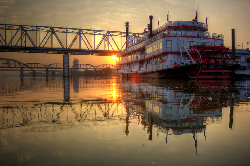 Riverboat Reflection<br /> The sun rising while the river is peaceful and calm showing off how reflections can be in moving water.  Couple kayakers to the left in the center of the river as well.