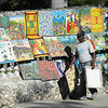 haitians love their art. it is everywhere and this man is setting up his stall in the early morning.