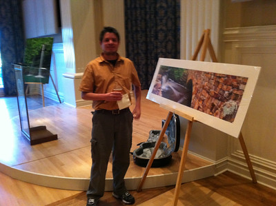 """Brian Cormack stands beside his photo """"Between Lake Bailey and Davies Bridge"""" at the LR Firehouse Hostel benefit at the Arkansas Governor's Mansion on September 8th, 2011. Behind Brian is a guitar autographed by members of U2 which if not so large, would be in Brian's pocket."""