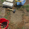 The original pieces are moved to the side. The pins mark their original location. I level the ground and lay down 3 inches of gravel in a shallow depression about 2 feet in diameter. The gravel is tamped down with a rubber mallet. The headstone base is placed in it's original position and using a combination of tamping and moving gravel, is made level and plumb. It feels really solid and I know the gravel will allow melting snow and rain to drain away from the stone and reduce the likelihood of frost heaving the soil.