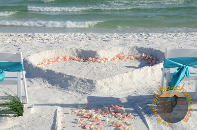 Coral and Cream Rose Petals Spread on the Edge of the Heart in the Sand