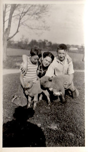 Mom with Paul and John on the farm. Is John holding a Hershey bar??