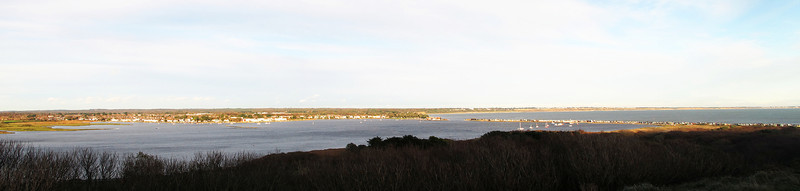 A panorama shot of Christchurch Harbour to the left across to the sandy spit on this side and Mudeford Quay on the far side of the harbour entrance.