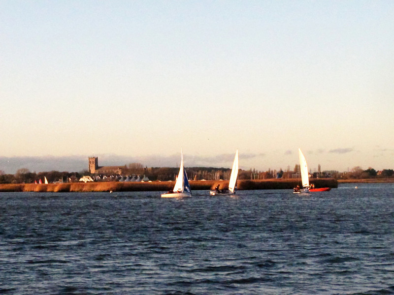 Sailing lessons in the late afternoon sun in Christchurch Harbour, with the Priory in the background.