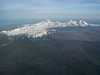 Broken Top and the Three Sisters are a snowy island surrouded by forest.