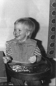 The high chair came into use again when my son Chris was young.  As a mom, I discovered that the old chair (which I had to have repaired and re-caned) was impractical.  The cane seat was hard to clean, so I made a vinyl cover to keep food out of the caning. The tray wasn't removable -- another cleaning challenge.  When Chris was tiny, we had to put something thick (e.g., the Manhattan telephone book) behind him to fill the extra space.  When he grew bigger, it was hard to lift him into this chair. (The tray would no longer swing over his head.)  Although I loved that old wooden high chair, I gave up and bought a modern metal & plastic one, with a tray that was removable, washable, and adjustable to the size of the child.