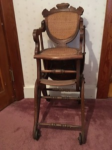 High chair with its tray swung to the back.