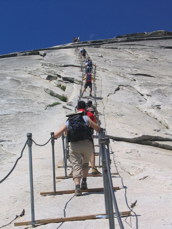 "it was just before 11am, and i started ascending the cables ahead of cris, jenni, grace, and alex.  i could not match their pace on the cables, however.  as you can see, the cables were attached to the top of two poles about four feet apart horizontally.  a wooden plank went across the two poles.  these ""steps"" were about 10 feet apart."