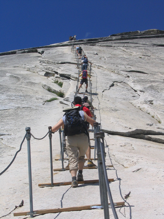 """it was just before 11am, and i started ascending the cables ahead of cris, jenni, grace, and alex.  i could not match their pace on the cables, however.  as you can see, the cables were attached to the top of two poles about four feet apart horizontally.  a wooden plank went across the two poles.  these """"steps"""" were about 10 feet apart."""