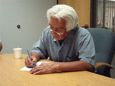 Larry Littlebird signing closing document for Hamaatsa's land purchase, July 31, 2007.