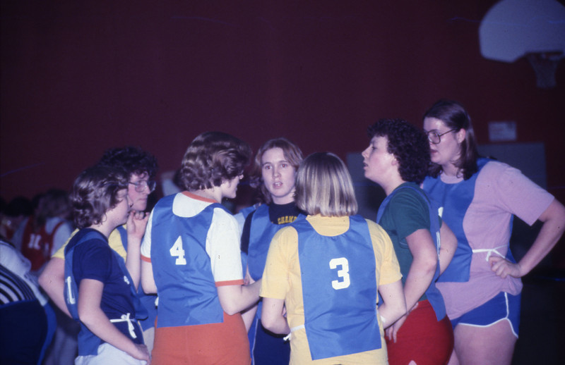 Students in a huddle during a basketball game, 1978