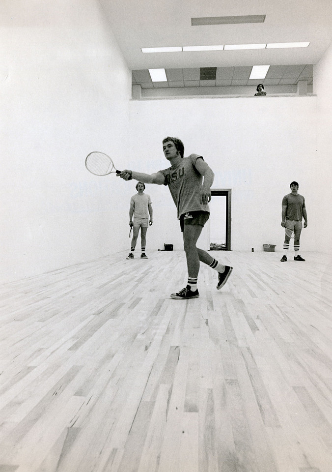 Student playing racquetball is friends on a court, 1977