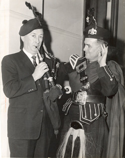 Frank McGovern, Grand Marshall of St. Patrick's Parade, gets lesson from John Duggan of St. Lawrence O'Toole Pipe Band of Dublin, 1960.