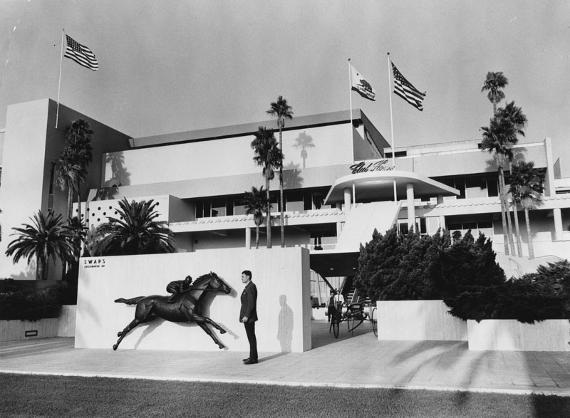 . Donald A. Voorhis, 40, a management assistant at Hollywood Park, is pictured in front of the track\'s club house near famed statue of Swaps, one of the great thoroughbreds of American racing history on October 27, 1960.   (Los Angeles Public Library)