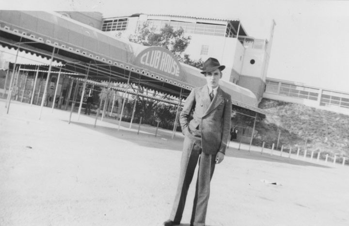 . Young man standing outside the Club House at Hollywood Park, Christmas, 1937.   (Los Angeles Public Library)