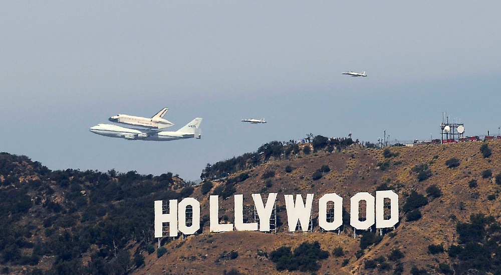 . HOLLYWOOD: With a touch of show-business flair, Endeavour, riding on the back of a modified Boeing 747, flies close enough to have its picture taken with the Hollywood Sign en route to LAX on Friday. 9/21/12 (John McCoy/L.A. Daily News)