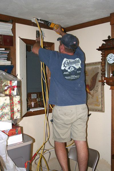 Ronnie cuts hole to get wiring to fuse box in the basement.