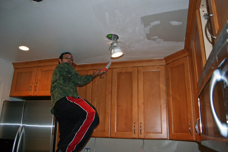 Calking tops of cabinets.