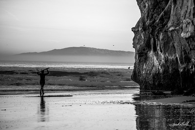 Lone surfer walking to enter the ocean
