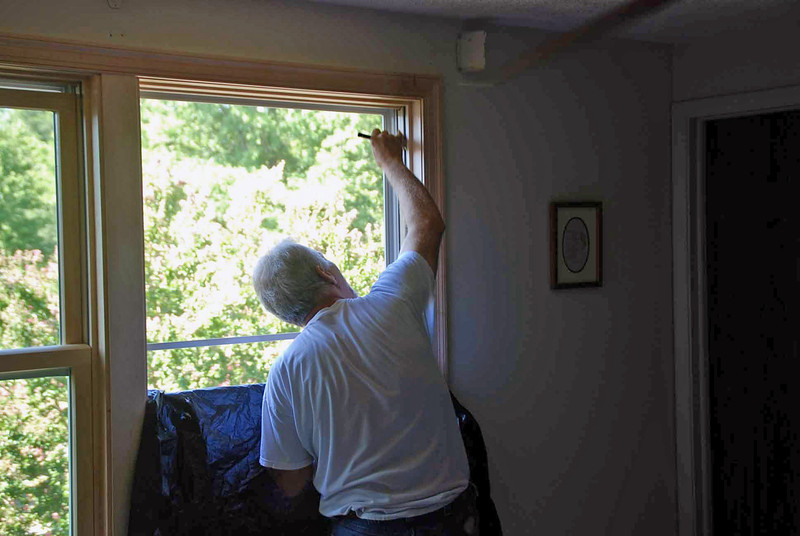 Putting clear coat acrylic on the master bedroom windows.