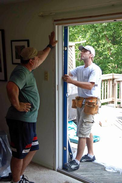 Installing the sliding glass door frame.
