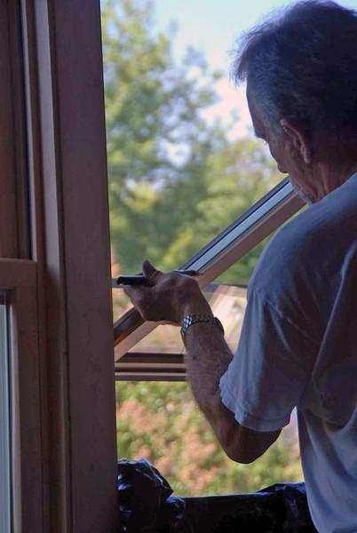 Putting acrylic coat on the master bedroom windows.