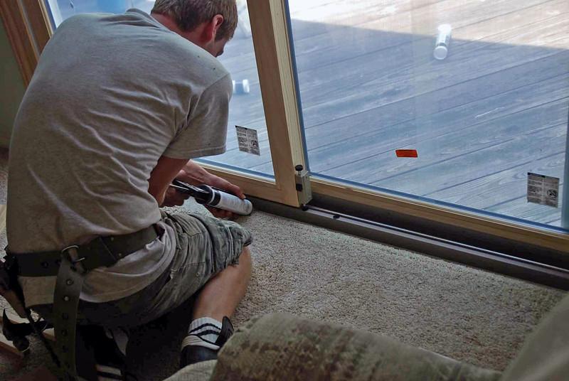 Installing the sliding glass door sill.