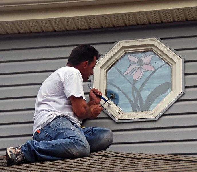 Removing the damaged portion of the stained glass window frame.