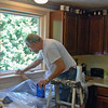 Preparing to put acrylic coat on the kitchen sink window.
