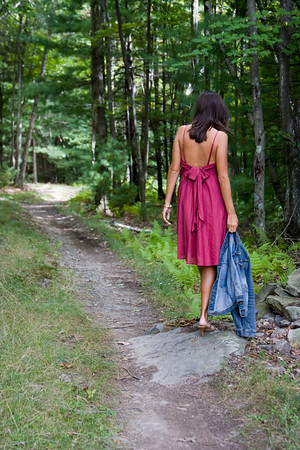 A woman walks away down a forest path.