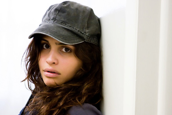 Woman wearing hat looks pensively at the viewer.