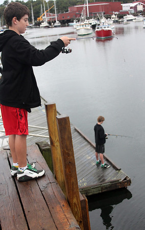 Allegra Boverman/Gloucester Daily Times. Tyler Malik, top, and Jack Colpoys, both 13, and eighth graders at Manchester Essex Middle School, were fishing for bait at the town docks on Friday afternoon. They plan to fish later on in the same area for stripers and bluefish with the bait they were catching.