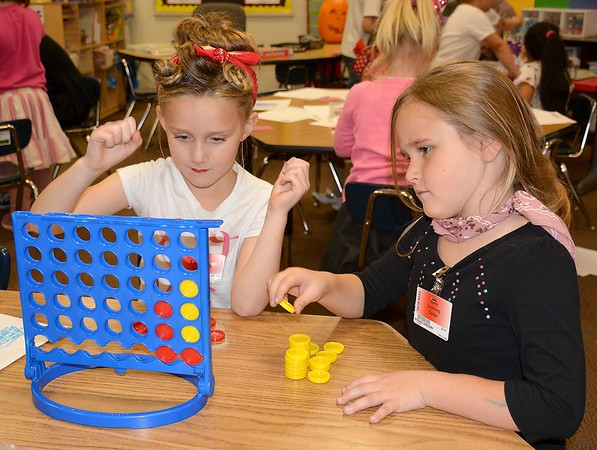Kindergartners Nora Hoekstra, left, and Kynlee Gregory, right, play a game of Connect Four during the Early Learning Center's 1950s-themed Halloween celebration Thursday. Kaitlin Cordes photo