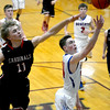 CHBC's Konner Blackerby shoots a layup just past the outstretched hand of North Clay's Brandon Repking at the Dieterich Holiday Tournament.