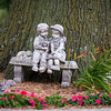A young couple cuddles on a miniature bench beneath a tree in the front yard.