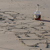 "JIm Vaiknoras/Gloucester Times: A half empty bottle of cognac sit near the words "" Long Live Dead Poets"" scratched in the sand in memory of local poet Vincent Ferrini on Niles Beach in Gloucester early Monday morning as part of Dead Poets Remembrance Day."