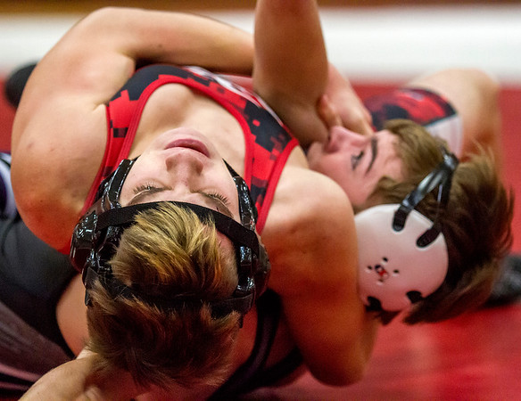 Effingham's Michael Cross, left, finishes off a headlock on Taylorville's Tyler Chesser for a pin in the 120-pound class contest.