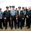 Allegra Boverman/Staff photo. Rockport Police Officer Roger Lesch, center, with his colleagues in the Rockport Police Department who walked his original foot patrol beat with him on his last day of fulltime work in the department on Monday. His beat started at Granite Pier and would stretch to the Cape Ann Tool Company down Granite Street.