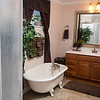 The master bath of the Jobe home features a circular shower enclosure and a clawfoot tub.