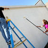 5-22-12<br /> Western HS seniors voluteer to clean up around the town of Russiaville on Tuesday. Kyle Ennis, Courtney Cossell and Mary James paint the back of the bank.<br /> KT photo | Tim Bath