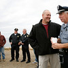 Allegra Boverman/Staff photo. Rockport Police Officer Roger Lesch, right, was surprised by his colleagues on Monday afternoon during his last fulltime day of work with the police department. As a surprise, they arranged to meet him at Granite Pier, to walk with him on his original foot patrol route from that location to the former Cape Ann Tool Company. Patrolman Dan Mahoney, next to him at left, brought him hot chocolate.