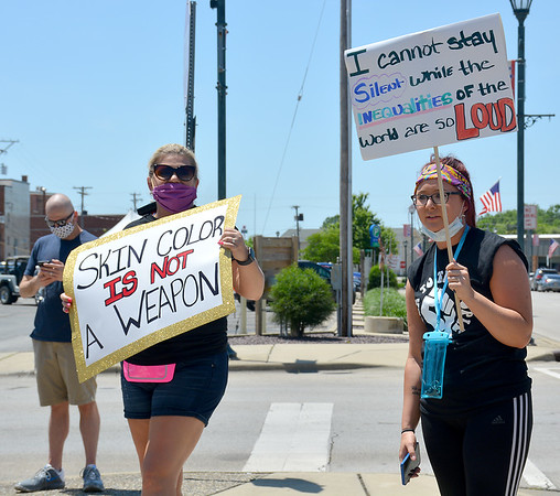 Heather Schmidt, left, and Kiaya Carey, right, both of Effingham, chant and hold up signs during a peaceful rally held by the Effingham Social Justice Group Saturday.