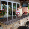 Ed and Alice Newell spend a lot of time relaxing on the porch of their pool house, which features a stone counter and bar in the outdoor kitchen and a lounge area with a television.