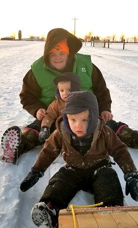 2 1/2-year-old twin brothers Eldon (front) and Victor (middle) Prins, enjoy their first sledding experience in the snow on their daddy's toboggan that he received for Christmas in 1994. Mother Samantha is in the back. Picture taken in Rural Altamont.