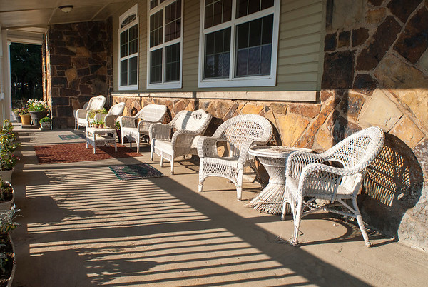 Rattan furniture offers an inviting retreat on front porch of the Jobe home.