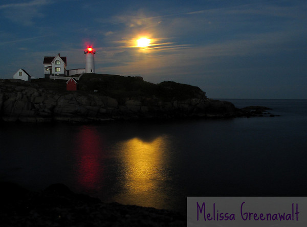 A full moon peeks out from behind iconic Nubble Lighthouse in York, ME.