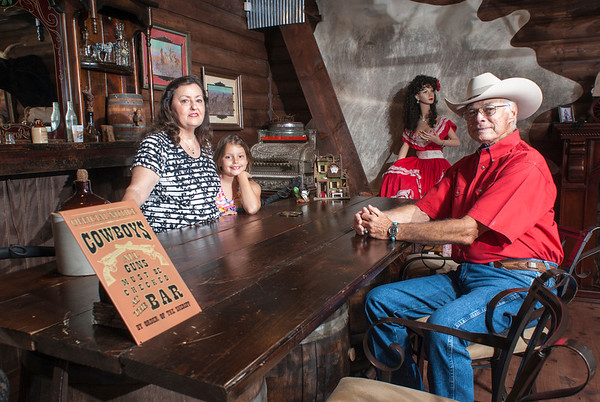 Kimber Hall, center, joins her grandparents Pat and Belienda Garrett in the Red Rose Saloon in their Wild West town. Pat made the bar out of an old waterbed and barrels.