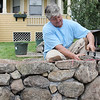 "Allegra Boverman/Gloucester Daily Times. Steve Pierce has been working to repair a stone wall at one of his properties he owns in Gloucester along Washington Street. The wall was damaged when a car hit it some time ago. He works on it with Dusty Rhodes of Gloucester when they can. Pierce used to do auto body work, so rebuilding stone walls is a new endeavor for him. ""It's not going to be pretty,"" he said of the work he's doing on the wall, ""but it's going to be functional."""