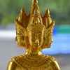 A 3 headed golden Buddha figure in a spirit house in Hua Hin, Thailand in August 2017